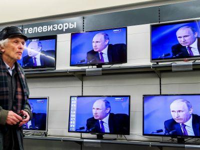 Владимир Путин на экранах всех телевизоров. Фото: Getty