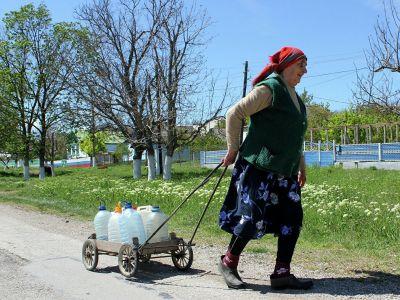 Жительница села Льговка Судакского района Крыма направляется за водой к уличной колонке. Фото: Юрий Лашов / РИА Новости